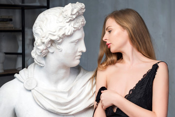 Young woman embracing God Apollo bust sculpture. Ancient Greek god of Sun and Poetry Plaster copy of a marble statue on grange concrete wall background. Ancient art and living beauty