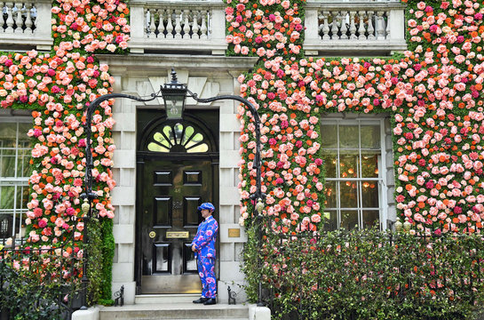 A doorman dressed in a floral patterned suit stands on duty outside of a private club with it's front covered in flowers in London