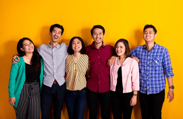 studio portrait of group of asian young friends looking at camera over yellow background Wall mural
