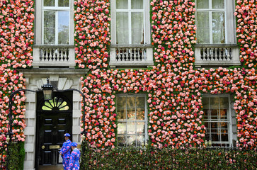 Doormen dressed in floral patterned suits stand on duty outside of a private club with it's front covered in flowers in London