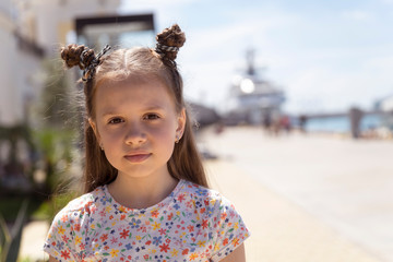 Portrait of little fashion girl on the background of the marina. Young photomodel with full lips