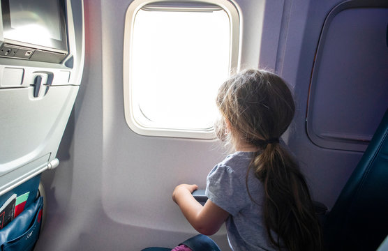 A toddler aged girl looking out the window of a airplane in flight.