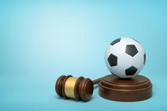 3d rendering of football on sounding block with judge gavel lying beside on light-blue background.
