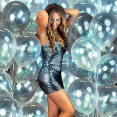 Beautiful young woman dancing in front of wall of party balloons in sexy  party dress