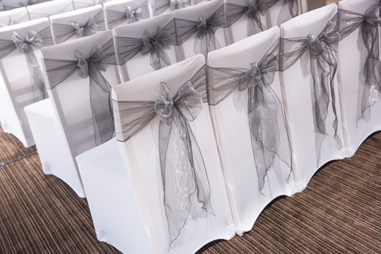 Covered chairs set for a party or wedding with bows