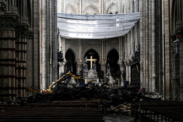 A picture shows rubbles and the cross at the altar, inside the the Notre-Dame Cathedral after it sustained major fire damage from the previous month, during the visit of Canadian Prime Minister Justin Trudeau in Notre-Dame Cathedral in Paris