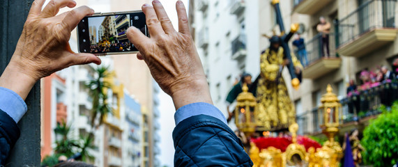 A man keeps on his mobile phone the image of the step of the Procession of Jesus the Nazarene in Huelva, Spain.