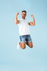 Excited emotional adult man posing isolated over blue wall background make winner gesture.