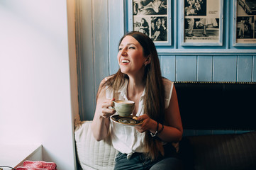 Stylish young woman laughs and drinks coffee in a cafe. Scarred with foam