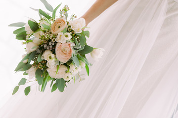 bride's hands hold beautiful bridal bouquet of white roses.