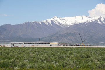 With snow-covered Flat Top Mountain in the background, construction workers build a new Facebook data center in Eagle Mountain