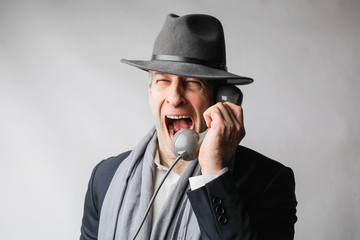 Man wearing a hat and shouting on the phone.