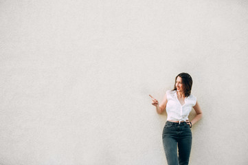 stylish girl in gray jeans and white t-shirt shows with a finger on the wall