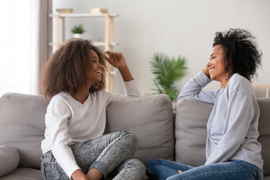 Happy African American mother and teen daughter chatting at home