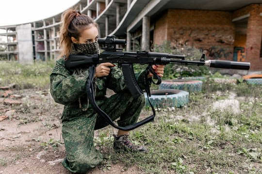 Armed woman in camouflage holding a rifle aims at the target. Women's army
