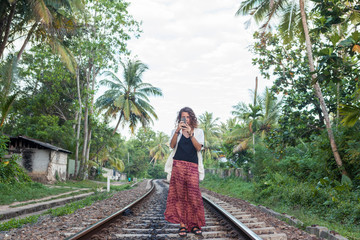 Caucasian girl taking picture with smartphone on train tracks Sri Lank