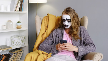 A man a metal head. Male rock musician uses mobile phone and chatting. Web camera. Paint face. Heavy metl. Strange man. Scary face.