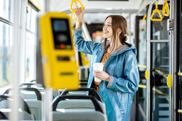 Young woman passenger enjoying trip at the public transport, standing with coffee in the modern tram Wall mural