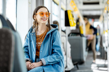 Young stylish woman dressed brightly enjoying trip at the public transport, sitting in the modern tram