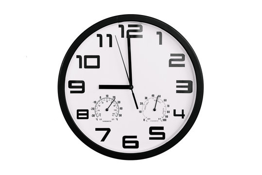 simple classic black and white round wall clock isolated on white. Clock with arabic numerals on wall shows 21:00 , 9:00