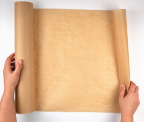 roll of brown parchment paper in female hands