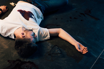 dead man with blood on t-shirt on floor at crime scene Wall mural