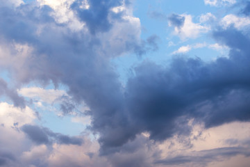 Epic dramatic storm cumulus fluffy clouds in sunlight against blue sky background, heaven texture