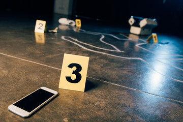 chalk outline, smartphone with blank screen and evidence markers at crime scene