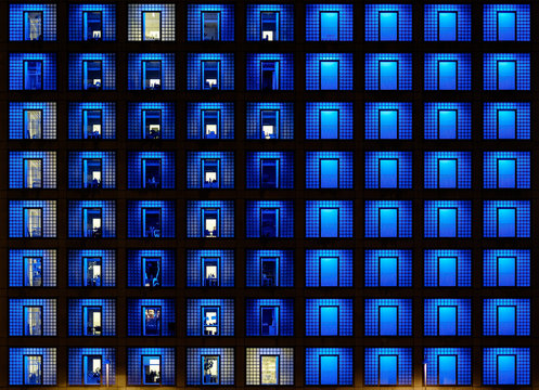 Illuminated wall of windows of high rise building
