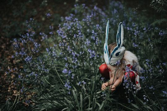 Girl wearing rabbit mask crouching in field
