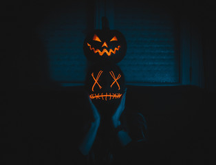 low light photography of person holding Jack-'o-Lanterns