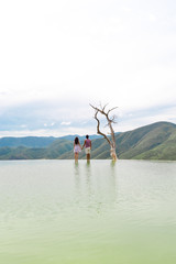 man and woman standing near tree on river during daytime