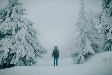 man standing on snow field between trees