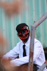 man wearing black and red mask while sitting on staie