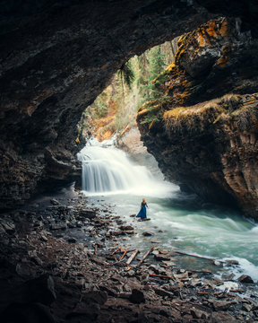 person standing on cave facing waterfalls