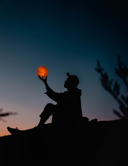 silhouette photography of person holding sun