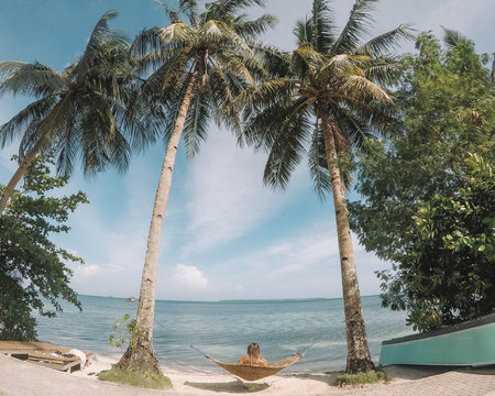woman sitting on hammock between two coconut trees on seashore during daytime
