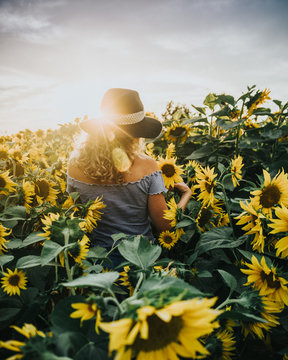 woman standing between blooming sunflowers during daytime