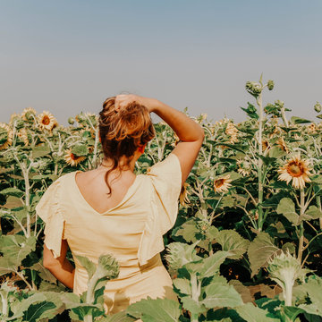 woman standing in front of bed of Sunflowers