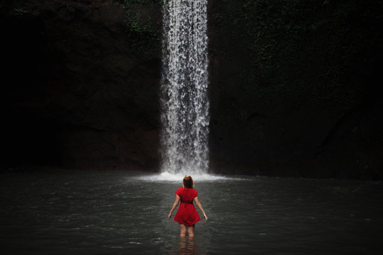 woman standing in-front of waterfall