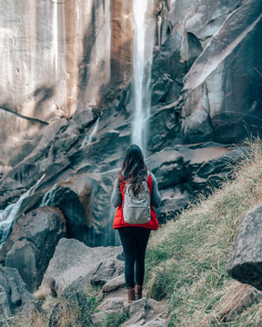 woman standing in front of water falls
