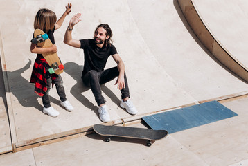The young father and his son dressed in the stylish casual clothes are sitting and have fun together on the slide next to the skateboards in a skate park at the sunny warm day