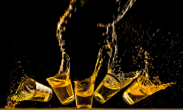 Five golden tequila shots dropping on bar