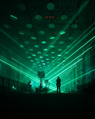 silhouette image of person standing on stage with green strobe lights