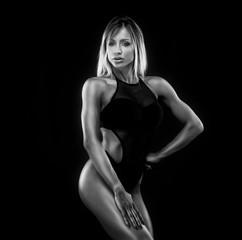 Sensual blonde woman posing in  black fashionable lingerie. Girl looking at camera. Athletic build.Studio shot.