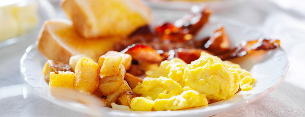 breakfast with eggs bacon and hashbrowns panorama