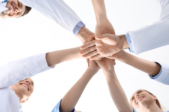 Team of medical doctors putting hands together on white background, closeup. Unity concept