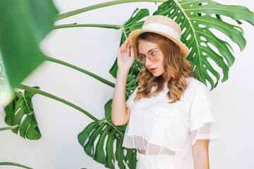 Wall Mural - Close-up portrait of lightly tanned girl in elegant hat looking with serious face expression to camera. Pretty young woman in stylish attire with blonde curls posing on white background with plant.
