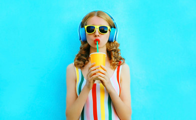 Portrait stylish woman drinking fruit juice listening to music in wireless headphones on colorful blue background Wall mural