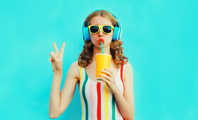 Photo sur Plexiglas Magasin de musique Portrait cool girl drinking fruit juice listening to music in wireless headphones on colorful blue background